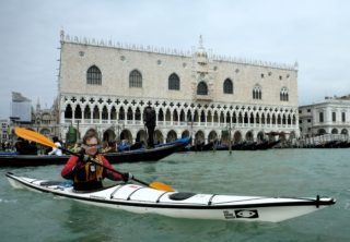 Man at San Marco with gondola and Palazzo Ducale (press photo)