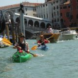 Couple paddling down a busy Grand Canal with motorboats